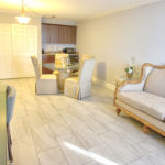 suite living room with sofa, TV, dining table with 4 chairs and kitchenette