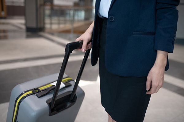 Close up of woman wearing skirt and jacket standing near her luggage in hotel