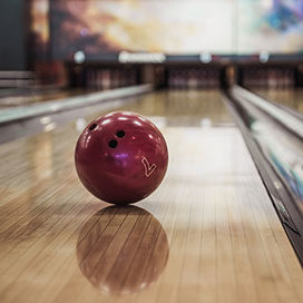 bowling ball rolling down line to hit pins